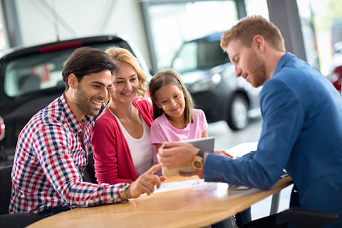 Progressive Ford - Happy family consulting with their salesman at the dealership