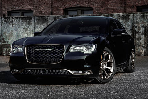 A black Chrysler 300 parked in a paved lot in front of a concrete wall and a brick building behind it