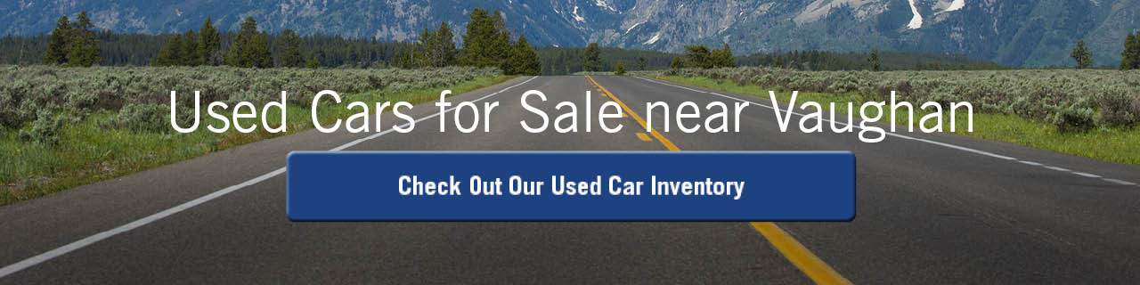 A banner showing a long, grass-bordered road going towards a mountain with the words 'Used Cars for Sale near Vaughan' across the top in black, and a blue button that says 'Used Car Inventory' in the middle. The button turns gray on mouseover.