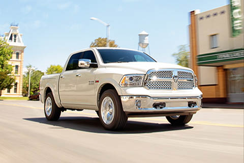 A pearl white Ram 1500 driving through a small town on a sunny day