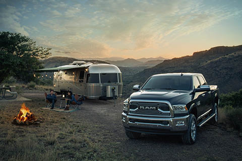 A black Ram 2500 parked near an old-fashioned camping trailer near a campfire and some mountains in the distance at dusk.