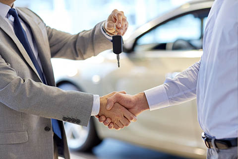 Downsview Chrysler - Salesman holding keys while shaking hands with customer at the dealership
