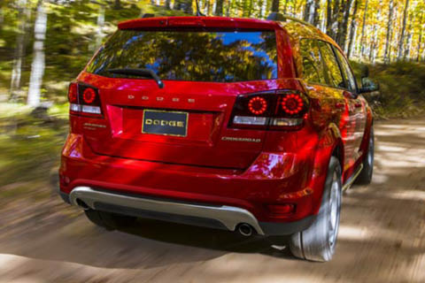 A red Dodge Journey driving down a forest path