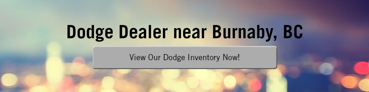 A banner with blurry city lights in the background, the words 'Dodge Dealer near Burnaby, BC in black along the top, and a blue button that says 'View Our Dodge Inventory Now!' in the centre. The button turns gray on mouseover.