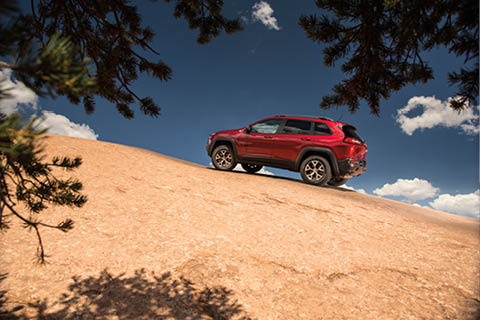 A red Jeep Cherokee Trailhawk climbing a smooth rocky hill