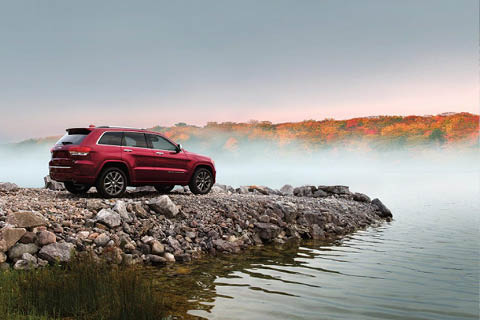 A red Jeep Grand Cherokee parked on a stone jetty overlooking a misty lake with autumn trees in the distance