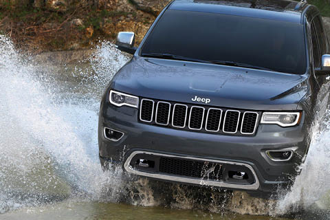 A blue-gray Jeep Grand Cherokee driving through a shallow creek