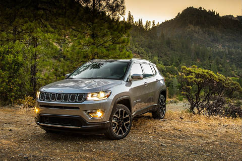 A gray Jeep Compass driving along a wooded mountain path