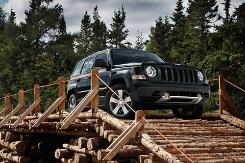 A black Jeep Patriot crossing a log bridge in front of a number of pine trees