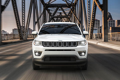 A white Jeep Compass driving towards the camera across a steel bridge, away from a small skyline