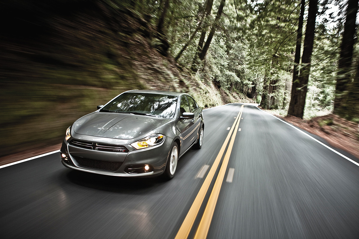 A gray Dodge Dart driving down a forest road