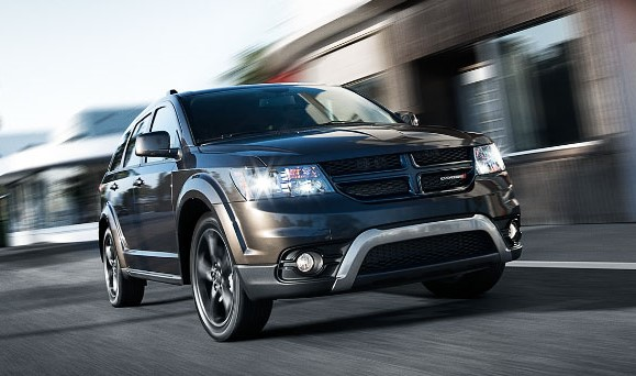 A black Dodge Journey driving along a small-town road