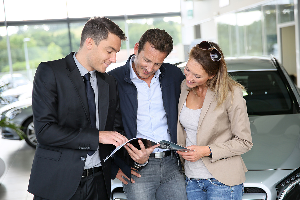 A man and a woman in a car dealership, reviewing the information in a brochure with an auto salesman.