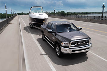 A black Ram truck towing a boat along a four-lane bridge
