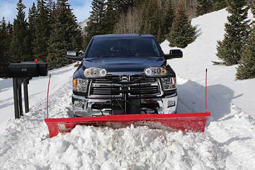 A black Ram truck pushing a plow through snow