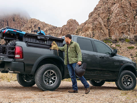 A photo of a man in a green jacket and blue jeans taking a bag out of a dark green Ram truck, loaded with an electric blue ATV, parked on a dirt road in front of a cloudy mountain