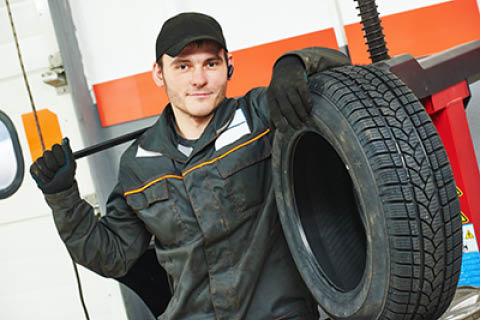 Kia West - Technician beside a tire