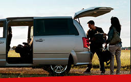 A man and a woman unloading a gray Dodge Grand Caravan along a grassy path. The side and rear doors are open.