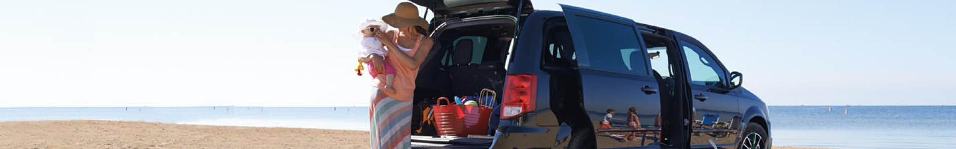A banner with a woman standing in front of a black Dodge Grand Caravan at the beach, holding a baby wearing sunglasses. The back and side doors of the Grand Caravan are open.