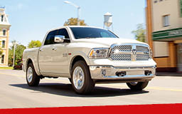 A white Dodge Ram 1500 driving down a suburban street on a sunny day