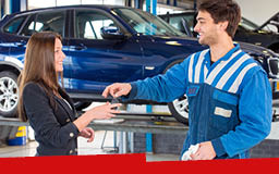 A technician in a striped blue uniform giving a set of keys to a woman in a black jacket, both standing in front of a blue car in a garage.