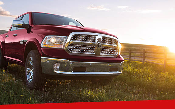 A red Ram 1500 in a sunny, grassy field in front of a wooden fence